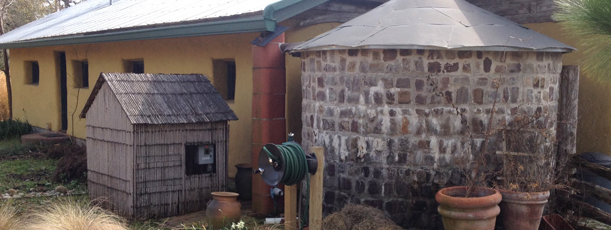 A stone rainwater tank outside of a house.